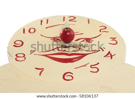 A low angle view of an old handcrafted wood toy clock face isolated on white with clipping path. Hand painted white with red numerals and a face at the center.
