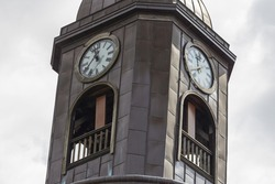 A low angle view of the turret clock on the grey tower on a gloomy day