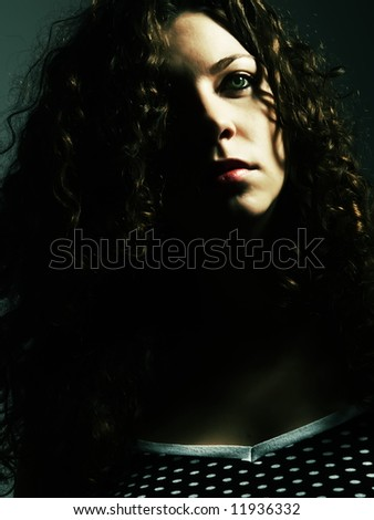 A low-key portrait about a pretty lady with white skin and long brown wavy hair whose look is enchanting and she wears a nice black dress with white dots