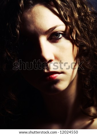 A low-key portrait about a pretty lady with white skin and long brown wavy hair whose look is attractive