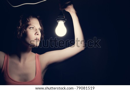 A low-key portrait of a girl holding a light.