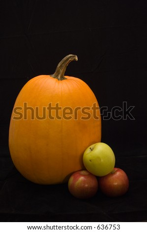 a low-key still life of a pumpkin, two red empire apples, and a golden delicious apple. - stock photo