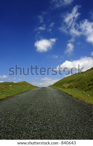 A low perspective on an uphill road in rural countryside.