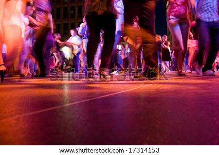 A low shot of the dance floor with people dancing under the colorful lights.