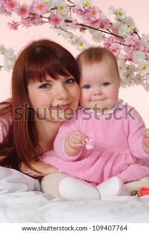 A luck Caucasian mother with her daughter lying in bed on a light background