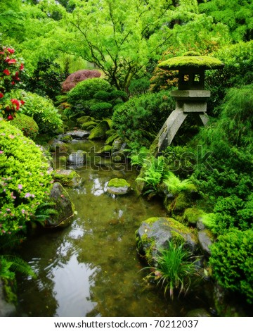 A lush green Japanese garden with Japanese lantern, and moss covered rocks.