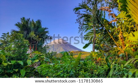 A lush tropical rain forest frames a beautiful Volcano in Arenal, Costa Rica.  #1178130865