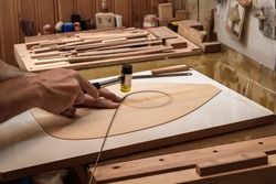 a luthier - instrument maker - inlaying ebony wood strips on the surface of soundboard to give point to whole outlines, guitar rosette.
