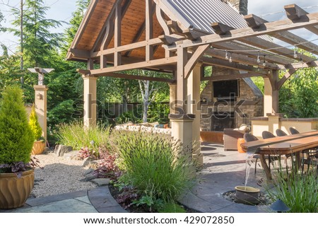 A Luxurious Backyard Patio Shelter, Complete With Fireplace, Sofa, And  Television.