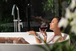 A luxurious girl is relaxing in a bubble bath with a glass of wine. Spa and relaxation