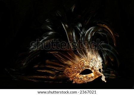 stock photo : A luxurious golden mask with long feathers on a black background