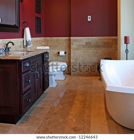 A luxury bathroom interior complete with granite and beautiful tiled floors and walls.