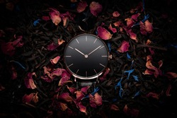 A luxury gold watch with a black dial. A watch on a beautiful stand, on a beautiful background of dried flowers, dried rose, colorful flowers. Woman / Man fashion