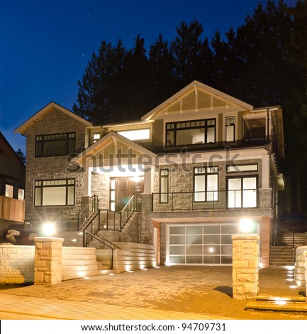 A luxury house with big driveway and the original garage doors in suburbs at dusk in Vancouver, Canada