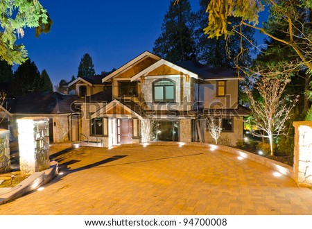 A luxury house with big driveway  in suburbs at dusk in Vancouver, Canada