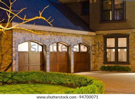 A luxury house with  three  garage doors in suburbs at dusk in Vancouver, Canada