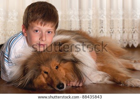 A lying on the floor serious boy is hugging his dog