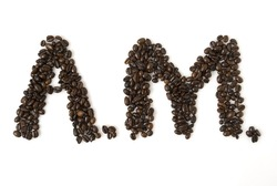 A.M. for morning written with coffee beans; shot against white background