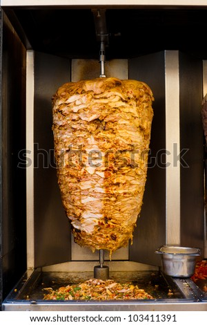 A machine slowly grills a skewered mass of chicken, a typical meat served inside a sandwich in the Middle East