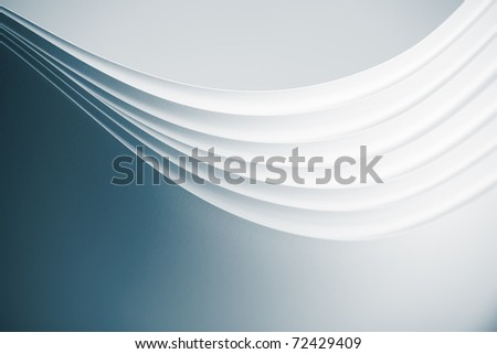 a macro, abstract image of several sheets of white paper arranged in a fluid, wave shape.