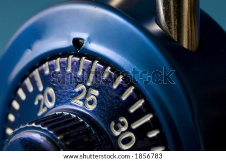 A macro (close up) image of a blue combination lock.  The number 25 is just past the tumbler and in sharp focus.