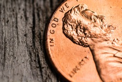A macro closeup of an Abraham Lincoln penny on a plain background.
