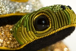 A macro closeup of the head and eye of a goldwork turtle.  Green threads run around the black of the eye, while other threads sparkle in soft focus in the background.