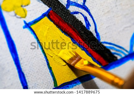 A Macro image of an artist painting a Queen of Hearts playing card on a canvas in their studio.  This very detailed and close up shot shows the artists brush dragging through the paint on the canvas. #1417889675