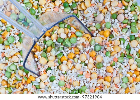 A macro photo of a bin of dry soup mix complete with clear plastic scoop.