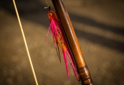 A macro shot of a wet pink instruder pacific salmon fly, fixed on a spey rod.