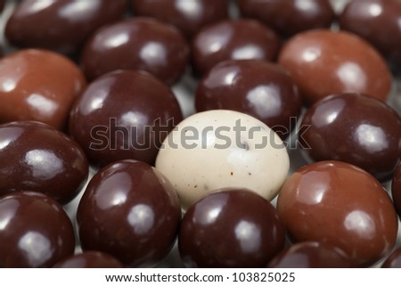 A macro shot of a white chocolate covered espresso bean surrounded by dark chocolate espresso beans. Shallow Depth of Field.