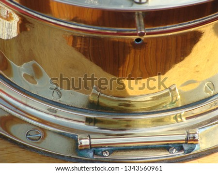 A macro view of the shiny reflective surface of an antique nautical commas in gold, yellow and gray. The schooner deck is reflected in the instrument. #1343560961