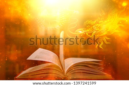 A magic book with a golden glow, shine and shine. An amazing story book with magical dragons full of power and success. And the glittering lights on the background #1397241599