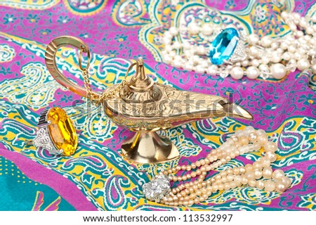 A magic oil lamp on top of gypsy clothing and surrounded by jewelry.