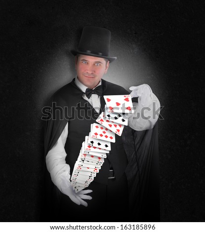 A magician has playing cards floating in the air on a black background for an entertainment or illusion concept.