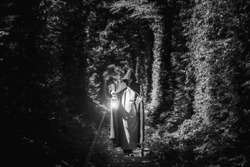 A magician in a cloak in a dark forest with a lantern. Black and white image. The concept of mysticism and fairy tales.