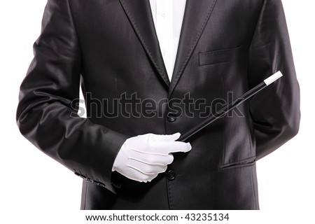 A magician in a suit holding a magic wand isolated on white background