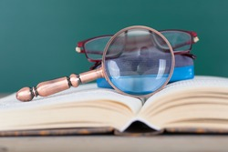 A magnifying glass, a blackboard eraser and a pair of glasses on the open book