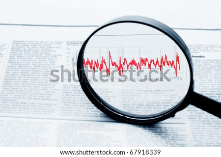 A magnifying glass focusing on a graph in the business section of the newspape