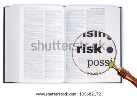 A magnifying glass held over a dictionary looking at the word Risk enlarged