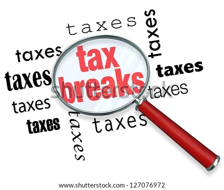 A magnifying glass hovering over the word tax breaks, symbolizing the advice and tricks that an accountant can use to increase deductions and save money when filing tax returns Stock photo ©