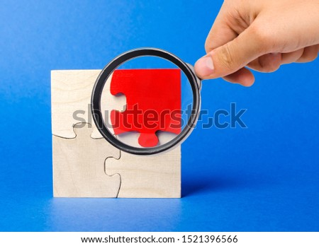 A magnifying glass looks at a red wooden puzzles on a blue background. Individual opinion. Stand out from the crowd. Uniqueness. Divergent views. Different concepts to other people. #1521396566