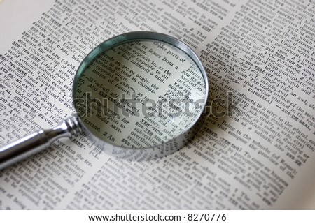 A magnifying glass sits on an old dictionary in natural lighting