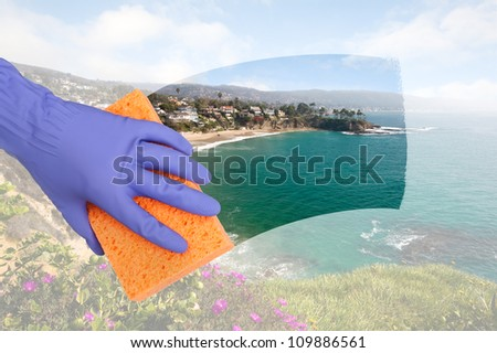 A maid cleaning windows on a cliff side home overlooking a cove along the ocean.