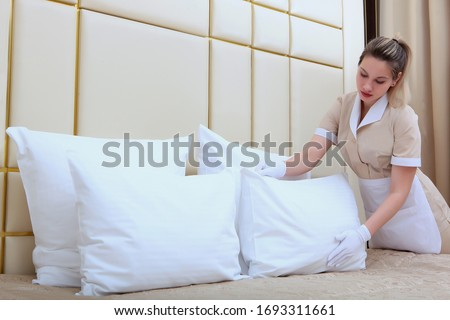 A maid in an expensive hotel adjusts the pillows in the bedroom. Cleaning the hotel room. Copy space. The concept of the hotel business.