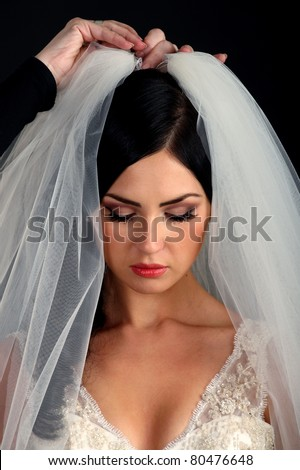 A maid of honor helping the bride with her wedding dress, isolated on black