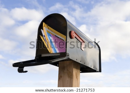 A mailbox full of mail against a blue and puffy white cloud sky