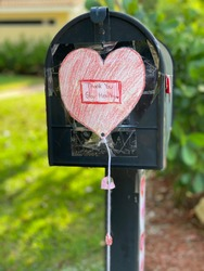 A mailbox outdoors with a beautiful paper heart drawn by a child that says thank you stay healthy.