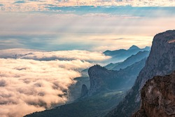 A majestic view of the rocky mountains and the valley in fog and clouds. Creamy fog covered the mountain valley in sunset light. Misty sunset over Crimea Mountains. Location place Ai-Petri, Crimea.