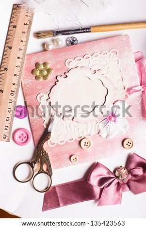 A making scrapbooking postcard with tolls and decorations on the table